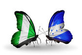 Butterflies with Nigeria and Honduras flags on wings — Stock Photo