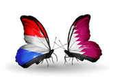 Butterflies with Luxembourg and Qatar flags on wings — Stock Photo