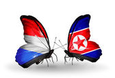 Butterflies with Luxembourg and North Korea flags on wings — Stock Photo