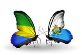 Butterflies with Gabon and San Marino flags on wings — Stock Photo