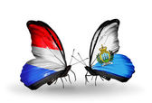 Butterflies with Luxembourg and  San Marino flags on wings — Stock Photo
