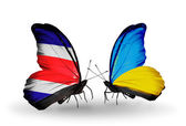 Kosta rika ve ukrayna bayrağı kanatlar üzerinde kelebekler — Stok fotoğraf