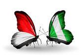 Mariposas con mónaco, indonesia y nigeria banderas en las alas — Foto de Stock
