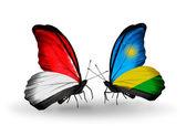 Motýli s monako, indonésie a rwanda vlajky na křídlech — Stock fotografie