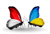 Butterflies with Monaco, Indonesia and Ukraine flags on wings — Stock Photo