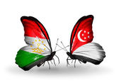 Butterflies with Tajikistan and Singapore flags — Stock Photo