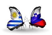 Fjärilar med uruguay och Slovenien flaggor — Stockfoto