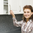 Woman opens a cupboard - Stock Photo