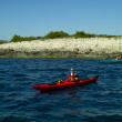 Sea kayaking with island behind - Stock Photo
