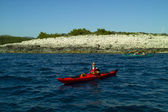 Sea kayaking with island behind — Stock Photo