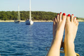 A girl put legs on the yacht — Stock Photo