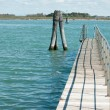 Stock Photo: Small bridge over blue lagunwater in Venice