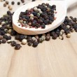 Stock Photo: Pepper corn mix in wooden scoop on old wooden table