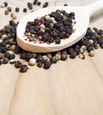 Pepper corn mix in a wooden scoop on an old wooden table — Stock Photo