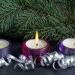 Christmas tree branch with three burning candle and ribbon over black background — Stock Photo