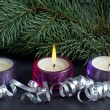 Christmas tree branch with three burning candle and ribbon over black background - Foto Stock
