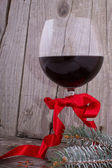 Red wine glass with Christmas decoration on the wooden table — Stock Photo