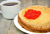 Pancakes with red caviar and a cup of tea — Stock Photo