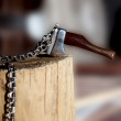 Miniature ax with a chain in the tree - Stock Photo