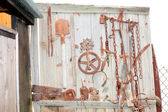 Old rusty tools and parts hung on fence — Stock Photo