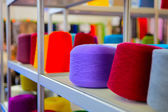 Spools of colored thread to sew on a shelf — Stockfoto