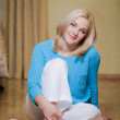 Smiling beautiful blond sitting on floor — Stock fotografie #37360169