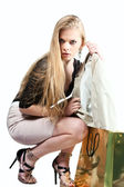 Young beautiful girl pulls the jacket of gold package isolated — Stock Photo