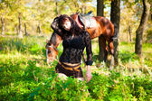 Young beautiful girl posing while lying on a background of forest and horses — ストック写真