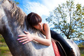 Sensual girl leaned over the horse neck — Stock Photo