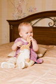 Baby with toy in pink dress on background of interior — Stock Photo