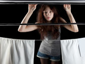 Beautiful girl behind window with white curtains — Stock Photo