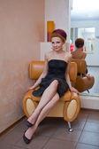 Seductive woman in black dress sit — Stockfoto
