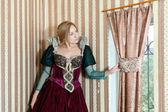 Blonde girl in medieval dress window — Stock Photo