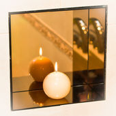 Burning candle on a spherical mirror shelf — Stock Photo
