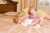 Young mother with her little daughter playing on the bed at home — Foto de Stock