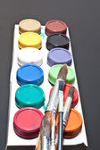 Brushes and colored paint artist on gray background — 图库照片