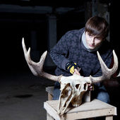 Young man working with a sharp deer skull in a dark basement — Stock Photo