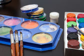 Brushes and colored paint artist on gray — Stock Photo