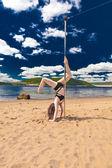 девушка сделать pole dance в купальнике на пляже фоне неба море и горы — Стоковое фото