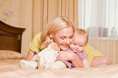 Young mother with her little daughter playing on the bed at home — Stock Photo