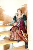 Actress  in medieval dress sitting on stairs — Stockfoto