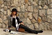 Drunk girl lies posing on stone wall background — Stock fotografie