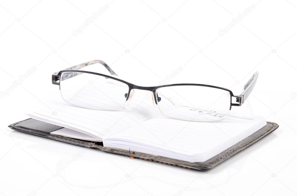 Notebook and glasses on white background — Stock Photo #12906285