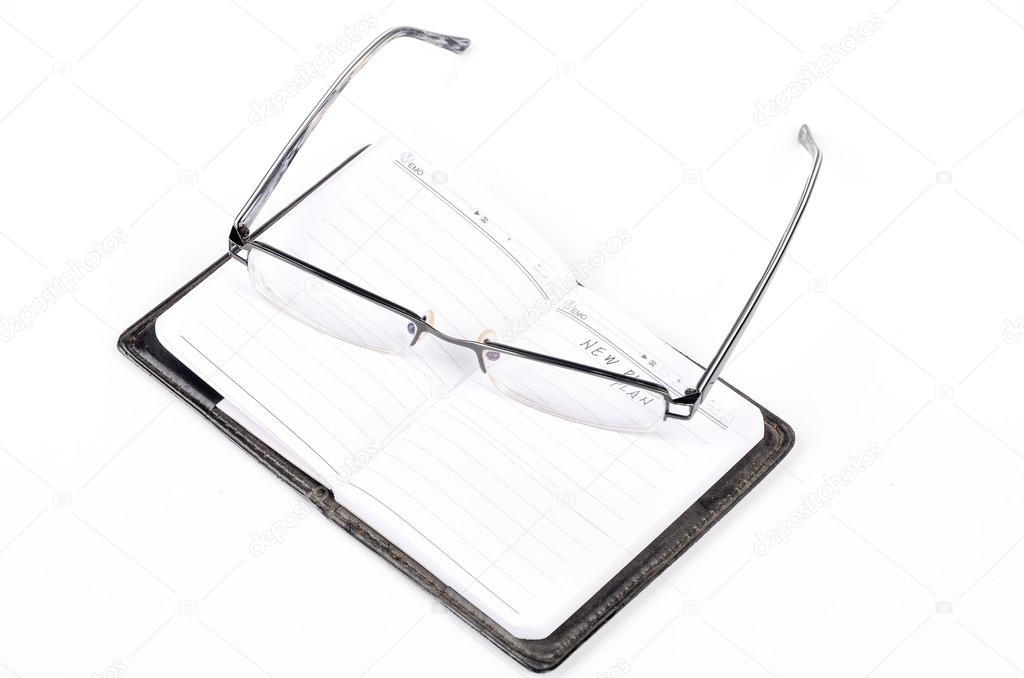 Notebook and glasses on white background — Stockfoto #12906563