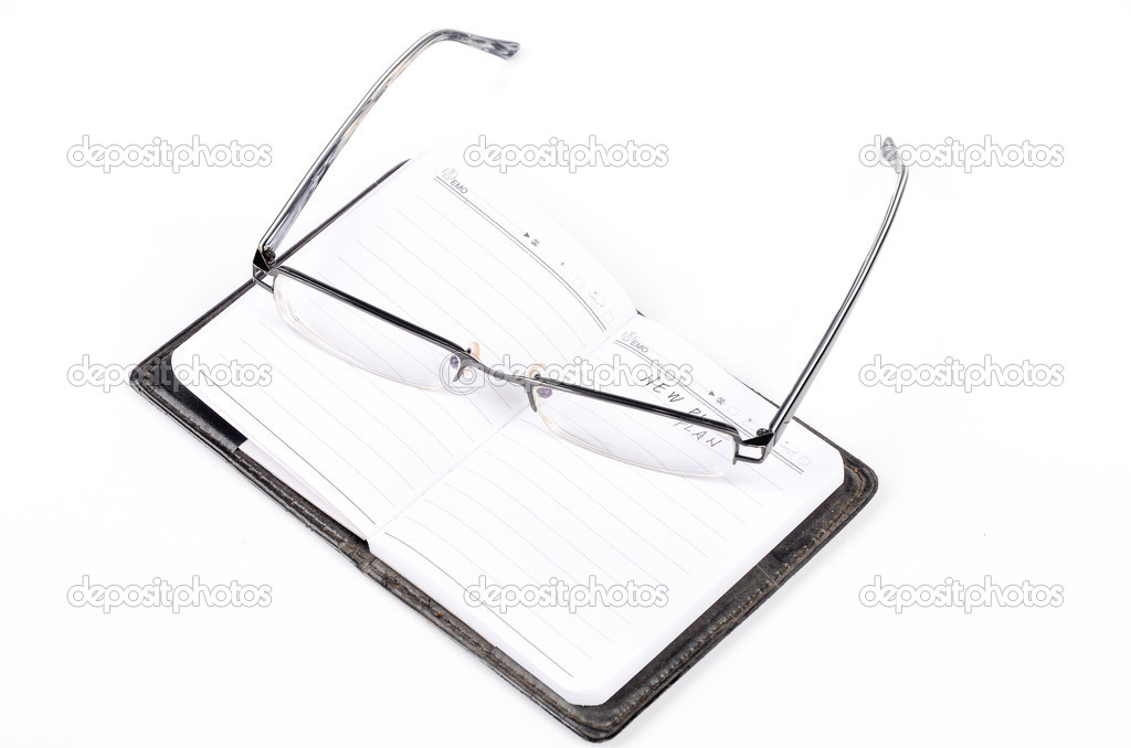 Notebook and glasses on white background — Стоковая фотография #12906563