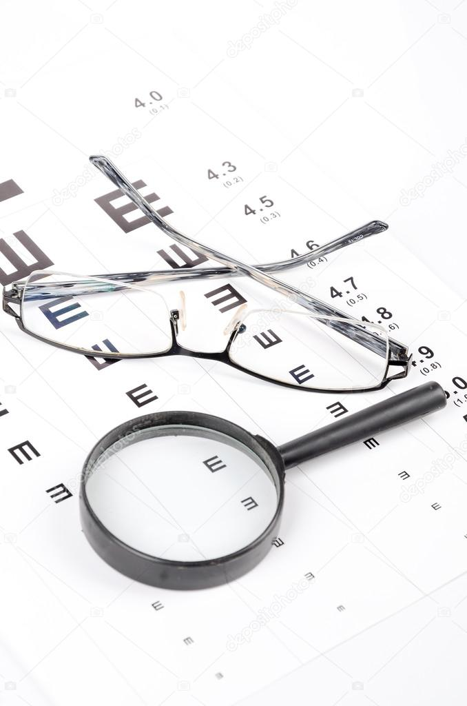 Magnifier and glasses on eye chart — Stock Photo #12921776