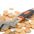 Wrench and coins - Stock Photo