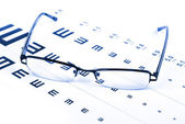 Reading glasses and eye chart — Stock Photo