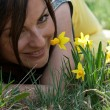 Young woman smelling daffodils — ストック写真