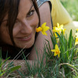 Young woman smelling daffodils — Stock fotografie